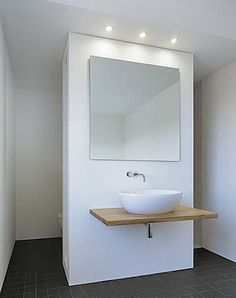 Toilet on one side, shower on another, both behind sink. Maatwerk Badmeubel type Donau