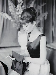 """The actress Audrey Hepburn photographed by Luc Fournol inside the boat """"Bateau Mouche"""" (on Seine), after a press conference for the publicity of her new movie """"Paris - When It Sizzles"""". Paris (France), July 16, 1962. Audrey was wearing: Dress: Givenchy (sleeveless, bodice of black satin with a ribbon at the waist in the same tissue and skirt of white silk, part of an ensemble with a short coat, of his haute couture collection for the Spring/Summer of 1962). Handbag: Givenchy (lined with…"""