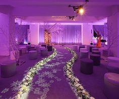 Motion-sensitive lighting created by Ira Levy projects white snowflakes that follow the couple as they walk down a purple aisle.