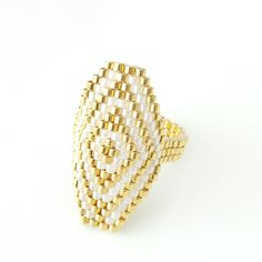 Bithiah, the Egyptian princess of the Pharaoh. An elegant, stately yet modern statement. Glimmering in gold and pearlescent white glass beads Beaded Jewelry Patterns, Bracelet Patterns, Beading Patterns, Diy Jewelry Rings, Beaded Rings, Beaded Spiders, Seed Bead Tutorials, Bead Loom Bracelets, Bead Weaving