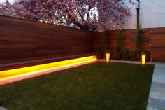 Wonderfully designed garden decor idea is shown in the image below. The renovation of the garden's corner is done with the integrated LED lights placed under the wooden walls of the garden. The floor is smartly covered with the balanced green grass to give this place a fresh feel.