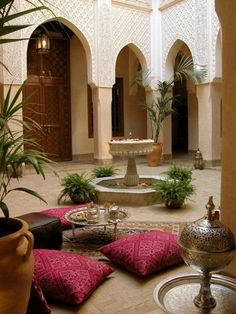 This Moroccan influenced room looks calm and serene with a fountain in the center and an area to enjoy tea.