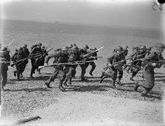 """Royal Marines charge the """"enemy"""" positions during landing exercises early in WW2. Note their regular army uniforms and kit little adjusted to the needs of a specialized """"storm force"""" charged with establishing bridgeheads under fire. Toward the end of the war though changes in equipment and tactics were well under way."""