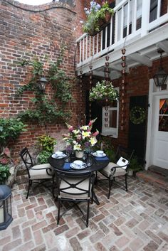 """The design takes advantage of the double height space by using a repeated element, Smith & Hawken Copper Rain Chains, along the length of the balustrade. A petite, traditional dining set, Smith & Hawken Allogio Collection, complements the traditional brick and New Orleans details found throughout the courtyard. The additions are selective and tasteful in order to highlight the great inherent qualities of the courtyard."""