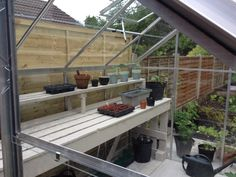 Painted greenhouse staging made from recycled pallets. Love it!!