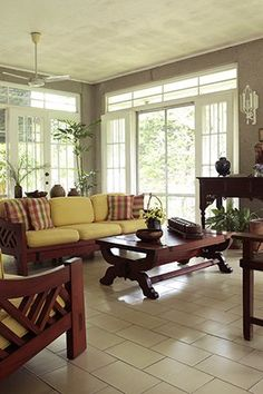 The living open layout and wide sliding doors allow fresh air and ample natural light into the home. The bright yellow upholstery and plaid pillows add a vibrancy that complements the dark wood furniture in the room. Dark Wood Furniture, Home Furniture, Outdoor Furniture Sets, Small House Interior Design, House Design, Interior Designing, Formal Living Rooms, Living Spaces, Filipino Interior Design