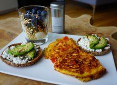 Frühstücks-Kombi: Zwei Toasties mit körnigem Frischkäse und Avocado, dazu ein Omelette mit Tomaten und Zwiebeln sowie ein Yoghurt mit gepufftem Quinoa und Heidelbeeren.