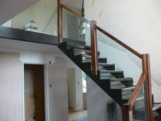 A steel staircase with stainless steel handrails and pan treads filled with concrete. All fabricated and fitted by Metcalfe.