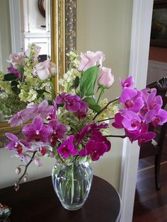 Entry Table Arrangement with Roses and Phalaenopsis Orchids. (Orchids are locally grown.)