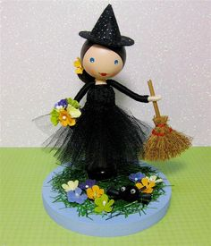 Little Miss Tricksy and Leggy the Spider Little Miss Tricksy is very far from frightening! Standing in a field of flowers along with her pet spider, Leggy, and carrying her very own broomstick..dressed in a black tulle tutu with a black lace bodice, topped with a sparkly black witches hat! She stands at around 21cm tall, including her hat and the base. The base is 11cm in diameter.