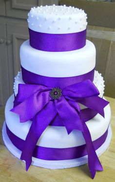 A purple and white 4 tiered cake elegantly dressed with royal purple satin ribbon and a beautiful broach.