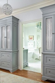 The entrance to the en suite bathroom is flanked by tall gray cabinets fitted with chicken wire doors draped in white fabric.