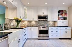 Simple white cabinets, dark shiny quartz and shiny glass mosaic tile.