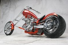 awesome red and orange custom chopper with belt drive that sits low to the ground with a highly chromed custom engine and exhaust.