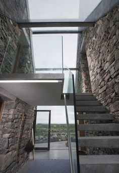 Connemara / Peter Legge Associates. Glass walls and concrete stairs join the two buildings.