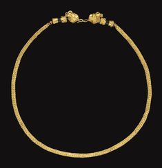 A GREEK GOLD AND BLACK STONE NECKLACE HELLENISTIC PERIOD, CIRCA 3RD-2ND CENTURY B.C. Formed of a length of three-fold double loop-in-loop chain, each end threaded through a capped cylindrical black stone bead, one end with a plain sheet cap edged with ropes, one end with filigree spirals edged with ropes, the terminals in the form of horned lion heads, petal-like ears on either side of the stylized looped horns, the back of the heads embellished with beaded filigree...