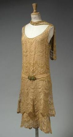 Dress, Chanel, ca. 1925. Ivory patterned, scalloped lace embroidered with glass beads. Low waist with belt of salmon silk crepe and golden metal buckle.