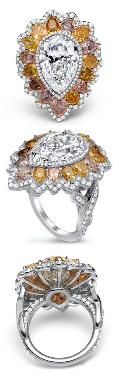 This platinum and 18K white gold ring boasting a very rare and striking 5ct. pear shape framed by 15 sensational pear shaped colored diamonds is an absolute behemoth. The multicolor diamonds are a dazzling motley of pinks, yellows, oranges, purples and browns. The center stone is delicately surrounded by a pear-shaped fringe of white diamonds while the colored diamonds are framed by a complementary fringe of slightly larger white diamonds.