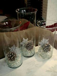 Marbles, glittery snowflakes, pincones and cylinder glass vases. I would bury a battery operated tealight candle in with the marbles for more sparkle.