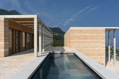 """Pergolas front these villas by David Chipperfield, comprising concrete columns and beams, as well as timber louvres. According to David Chipperfield Architects, they """"echo the rhythm of the surrounding olive groves""""."""