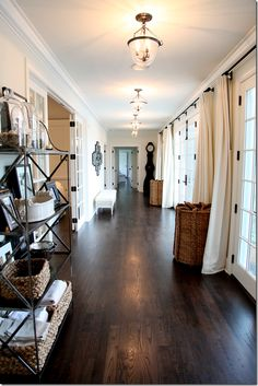 Cote de Texas, inspiration gorgeous home, stunning light filled hallway, dark floors, light walls. Same color walls AND same curtains throughout entire home.