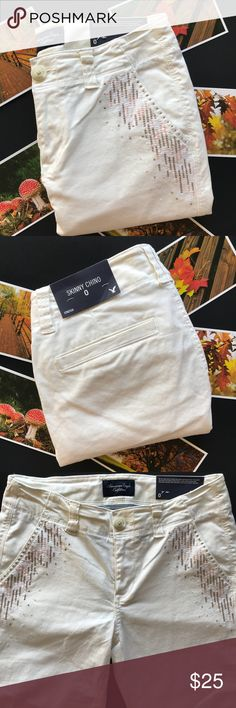 """American Eagle: white/cream skinny chino pants American Eagle Outfitters: white/cream colored skinny chino pants with brown, white, and pink sewn patterned near front pockets. Size 0 reg. Condition: new with tags. I do not see any flaws. They can be rolled like they came or unrolled. Approximate measurements laying flat: waist 14 1/2"""" front length unrolled 35 1/2"""" back length unrolled 36 1/2"""" inseam 28 1/4"""". Reasonable offers are always welcomed. Sorry no trades or modeling. American Eagle…"""