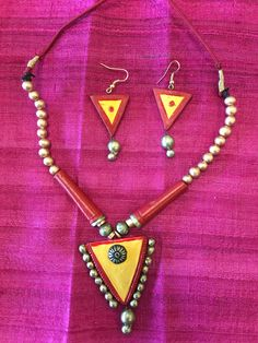 This is a very beautiful set of hand made and hand painted terracotta jewellery. It comes with a necklace and pair of earrings having vibrant colour combinations that compliment each other. - Necklace