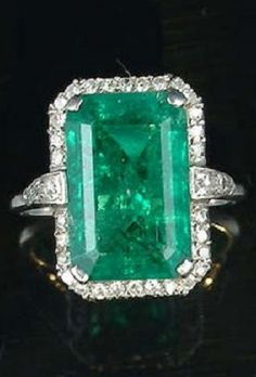 An early 20th century emerald and diamond dress ring the step-cut emerald, to a single-cut diamond border and shoulders, with carved scroll gallery. #Edwardian #BelleEpoque #ArtDeco #ring