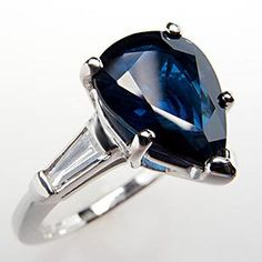 A gorgeous natural blue sapphire engagement ring featuring a high quality 2.3 carat pear cut center stone and gorgeous tapered baguette natural diamond accents stones. This certified ring is crafted of solid platinum and is in excellent condition.