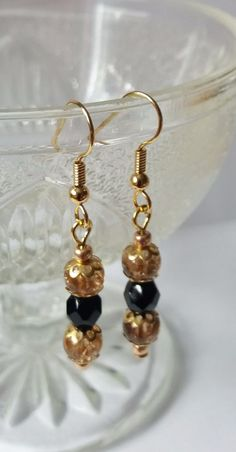 Light Brown and Black Crystal Earrings Elegant earrings with light brown crackle glass beads, black opaque crystals and gold plated elements
