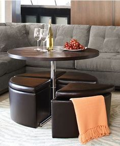 Brilliant idea! Coffee table turns to dining table. Seats are storage ottomans.
