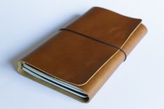 This refillable leather leather journal cover is designed to fit up to three journals. Its available to fit pocket size (9cm x 14cm/3.5in x 5.5in) (such as Field Notes or Moleskine pocket size cahiers), Moleskine large cahier size (13cm x 21cm/5in x 8.25in) and also A5 stapled notebooks such as Rhodia. The cover is cut from a piece of American made oil tanned leather. The leather is very flexible making this an ideal choice if you like a very tactile journal. This oil tanned leather is…