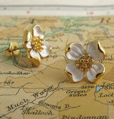 """Sculptural little dogwood blossoms measure just under 1/2"""" tall. White enamel leaves curl towards the center of the bloom, revealing a shiny gold-plated underside. A favorite among our staff - there's"""
