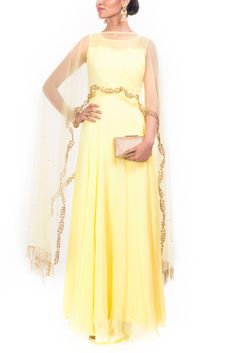 Featuring a yellow flare gown with long cape. The cape has a scallop embroidery on the hem There are beautiful embroidered frindges in both the ends of the cape. Sequins, cutdana and beads has been beautifully used to highlight the garment.