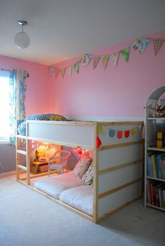 The bunting at the end of the bed is a really pretty color combo, and the mini-living room under the loft bed is darling
