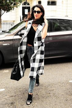 Amal Clooney wears a black tank, long plaid vest, skinny jeans, black booties, and black sunglasses