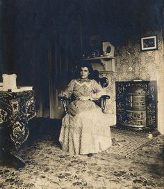 https://flic.kr/p/x8ZLAQ | At Home, Silver Halide Print, Circa 1905 | I love old photos that show the inside of average homes. It must have been a very colorful place: the wall paper was probably bright--maybe blue and green. The cast iron fire was shiny black, a richly colored Turkish carpet covered the table, a la Dutch Master painting, and the carpet's floral pattern must have been varied and lovely.