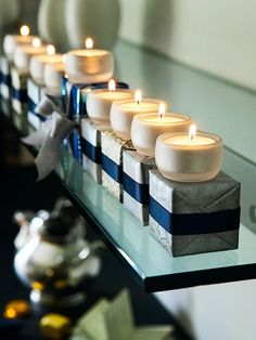 For a unique menorah, set glass tea-light holders on silver-and-blue wrapped boxes, securing the candleholders with double-stick tape. #hanukkahtablescape #hanukkahtablesetting #centerpieces #holidaydinnerideas #bhg
