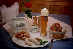 """Weißwurstfrühstück in München - Die Weißwurst ist eins der traditionellsten und bekanntesten Gerichte Bayerns. Stilecht wir diese bayerische Spezialität """"gezuzelt"""" und mit Brezn, süßem Senf und Weißbier serviert."""