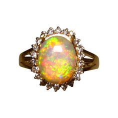 A beautiful Crystal Opal ring accented with a halo of 22 Diamonds in 14k Gold.  The oval Coober Pedy Opal is over 2 carats in weight and is very bright and colorful.