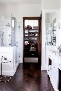 White master bathroom with dark wood trim and dark stained wood herringbone floor. A white master bathroom with dark wood trim leads to a walk-in closet filled with a dark stained closet island and shelves lined with Louis Vuitton bags. Chic master bathroom boasts a glass and wainscoted shower enclosure filled with gray mosaic marble tiles alongside a dark stained wood herringbone floor. wood-herringbone-floor-tile LIV Design Collective.