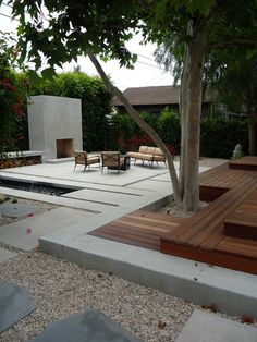 "I like that the courtyard walls are actually a hedge creating a softer feel and a ""green wall"". Love the outdoor fireplace and modern feel. I also like the gravel with the large stone pavers."