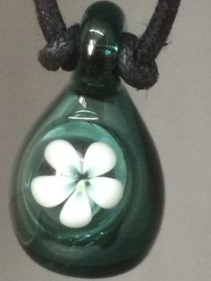 Outstanding white daisy on teal glass. To purchase, email info@oasisenergyt..., and reference TF1. $34 plus applicable taxes and shipping. Includes an eyedropper for filling with your favourite essential oil or blend. To purchase premium essential oils for your pendant, visit www.shopdoterra.com.