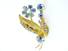 Aurora Borealis floral brooch. Dazzling AB rhinestones with gold tone leaves and flowers. Vintage pretty 1950s.