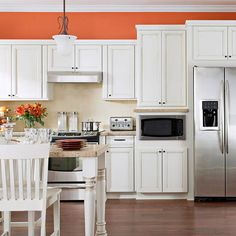 Sherbet Orange + White Sherbet-orange walls create a dynamic backdrop for the silhouette of staggered white cabinets accented with black hardware. Using warm neutrals for backsplash tiles and countertops leaves the drama near the ceiling, where it can call attention to the elegant woodwork.