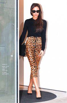 Victoria Beckham in a snug black sweater and a leopard pencil skirt