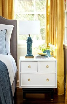 gray upholstered bed + teal & navy accents + golden yellow silk drapes