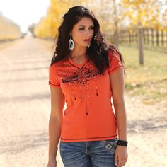 Every country girl loves a little glitz and glam; and this V-neck strikes it right by combining the perfect mix of style and shine in this standout orange top.  White and turquoise metal nail head details give this shirt that perfect bit of glitz. A unique black tribal graphic is featured on the front. Boasting a long and lean fit, this V-neck is flattering for every figure.   CTT9111017 ORG