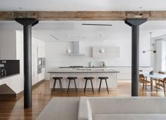 Minimalist white kitchen with an adjacent eating area in a restored Tribeca loft.