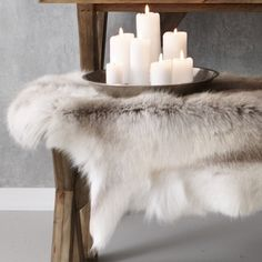 White candle display with fur on wood